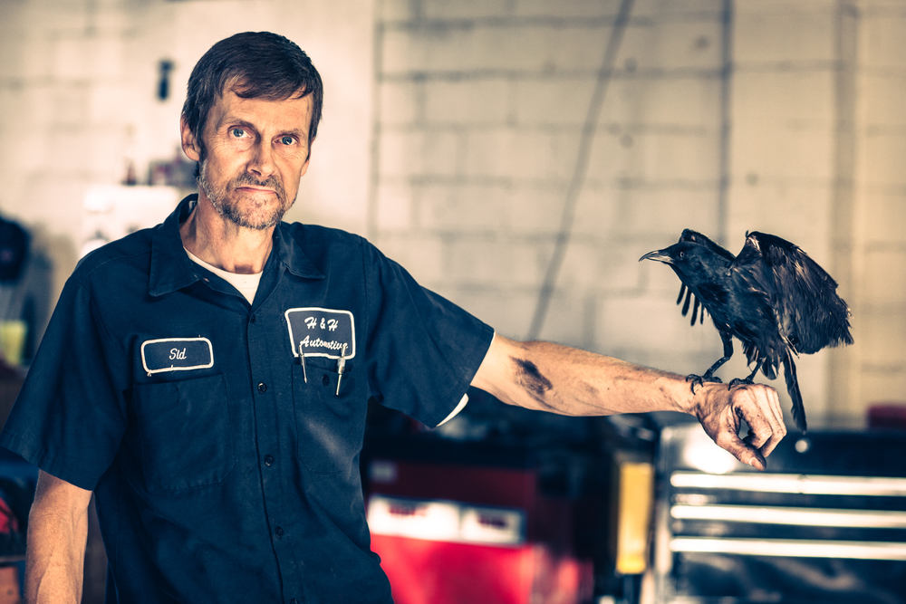 "Sid and his pet crow named ""Crow"" pose for a portrait at H&H Automotive in Athens, GA