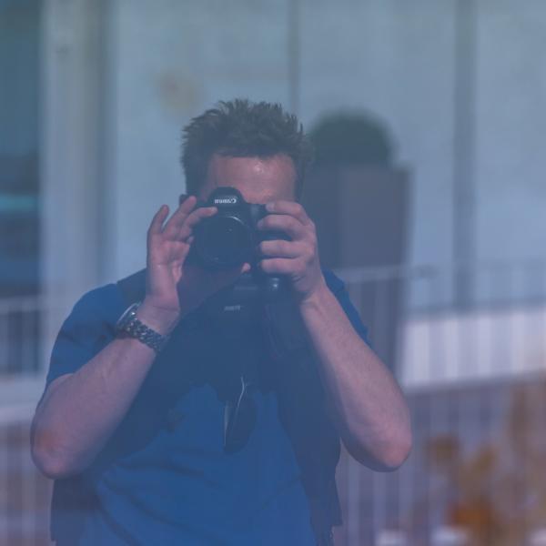 Behind the camera.