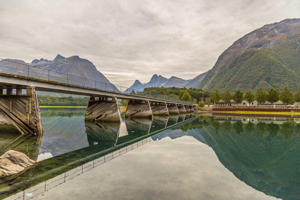 Rauma river  near  Åndalsnes, Norway.   This was taken during my drive from  Oslo  to  Ålesund  on a late Friday afternoon. Driving down the valley I saw the river was very calm and had a greenish color. There was such a beautiful scenery all over so I stopped the car and captured this photo with very nice reflections.