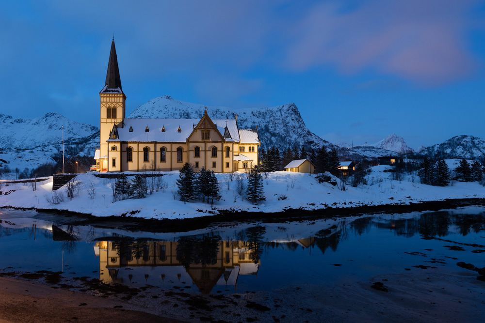 Svolvær, Lofoten. The Lofoten Cathedral mirrored in the clear water just after sunset.