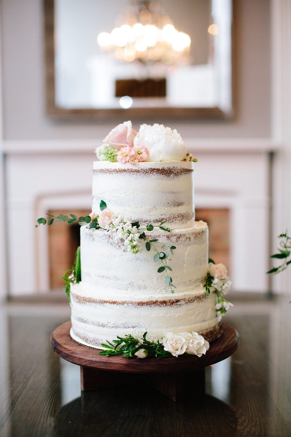 Partial naked wedding cake with flowers