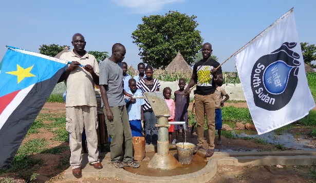 Ater Thiep, Salva Dut and John Mourwel with villagers at well outside WFSS compound in Wau.