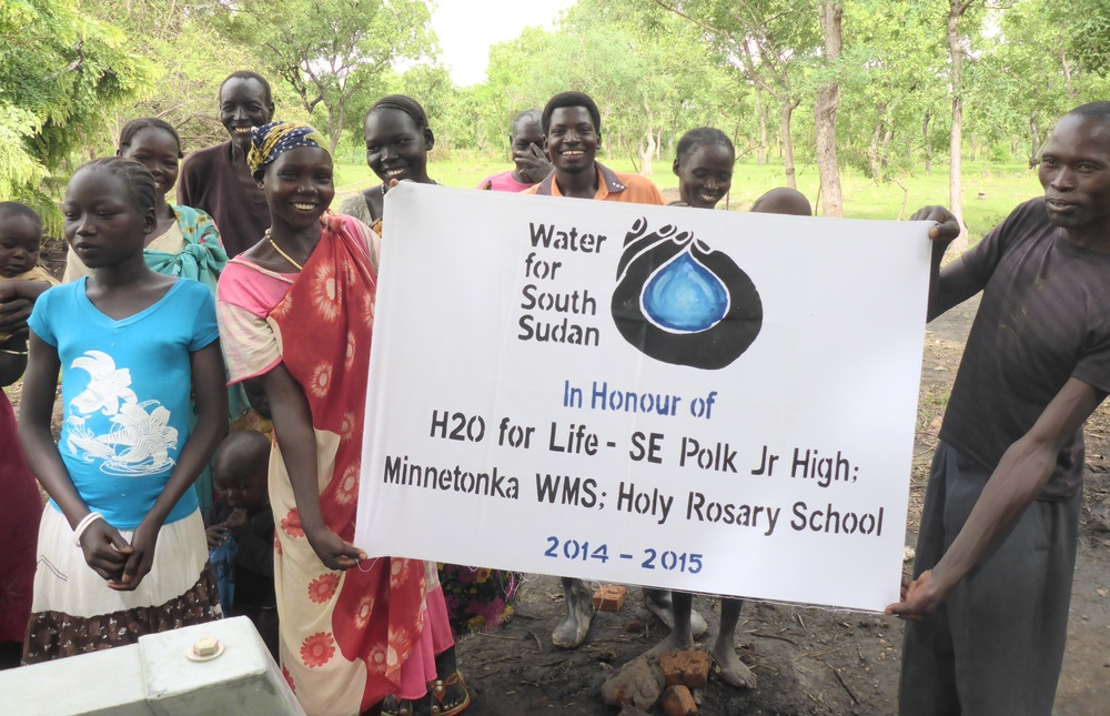 Villagers in Achuirdit, western bahr el ghazal state, proudly display well sponsorship banner.