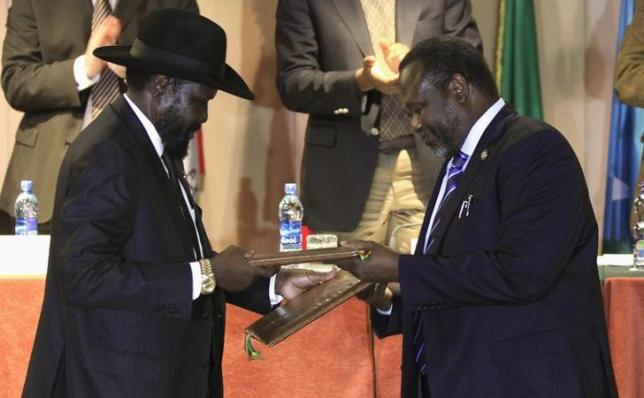 South Sudan's President Salva Kiir (L) and South Sudan's rebel commander Riek Machar exchange documents after signing a ceasefire agreement during the Inter Governmental Authority on Development (IGAD) Summit on the case of South Sudan in Ethiopia's capital Addis Ababa,. REUTERS/TIKSA NEGERI