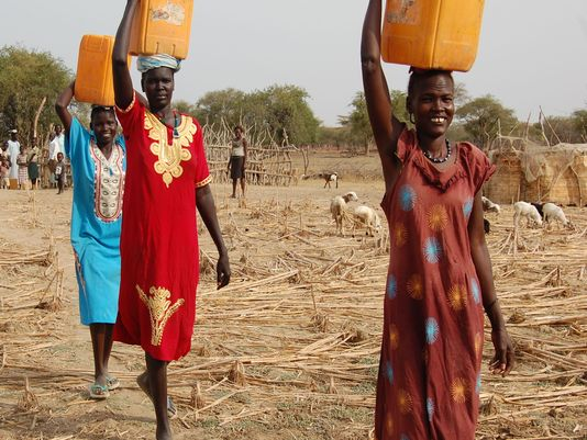 Women carry water in south sudan. photo by ben dobbin