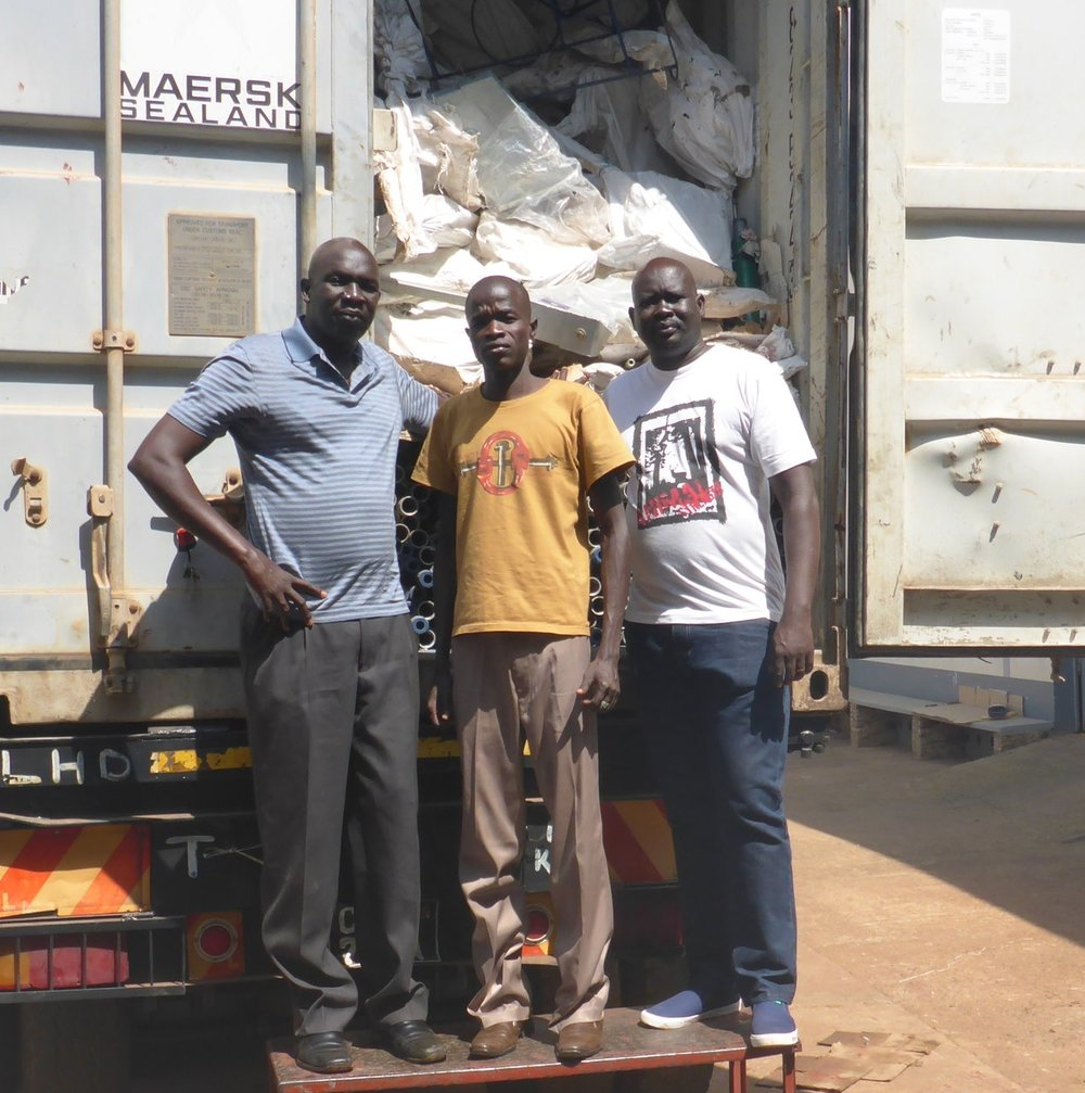 wfss country director ater thiep, hygiene manager mathew akuar and assistant country director aj agok with loaded supply truck in kampala