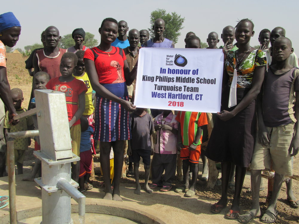 VILLAGERS IN Lueth-agok VILLAGE IN AWEIL EAST STATE CELEBRATE THEIR NEW WELl sponsored by king philip middle school in connecticut.