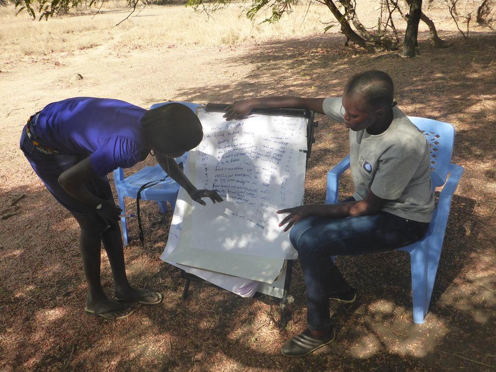 Participant reading through while Adau look on.JPG