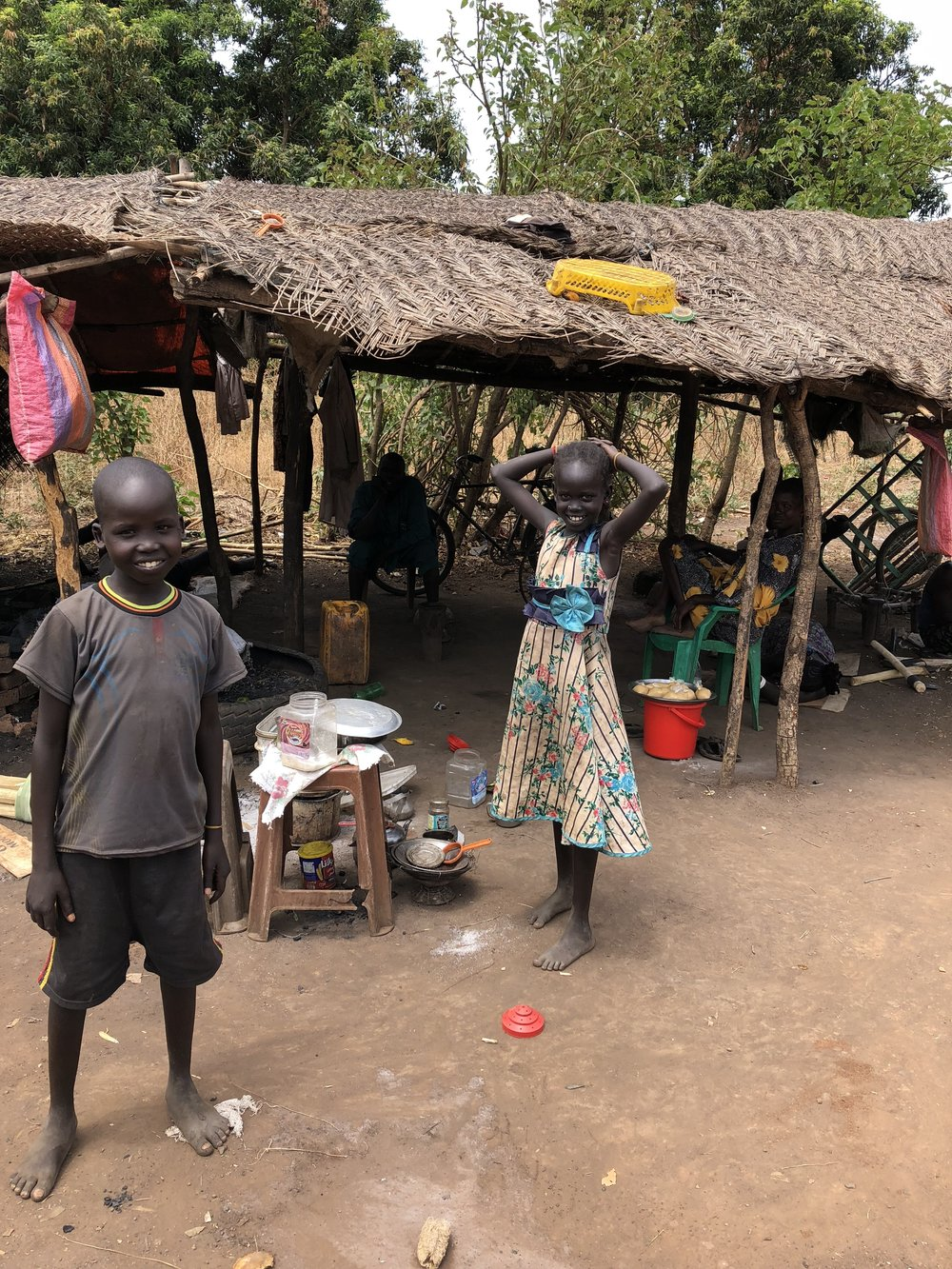 Children stand near a market in Wau.