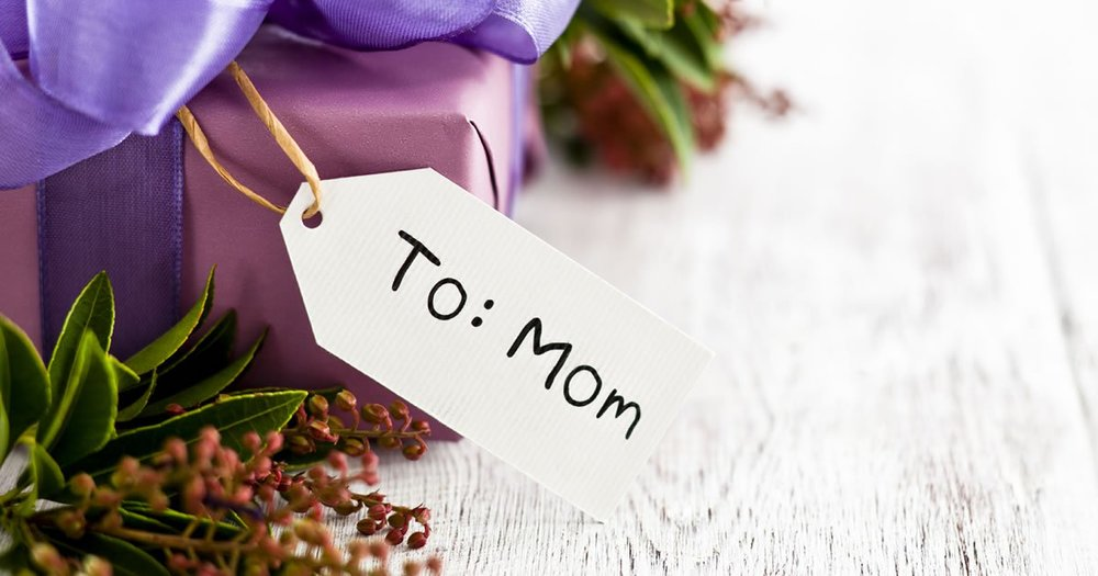 "Purple present with tag, ""To: Mom""."