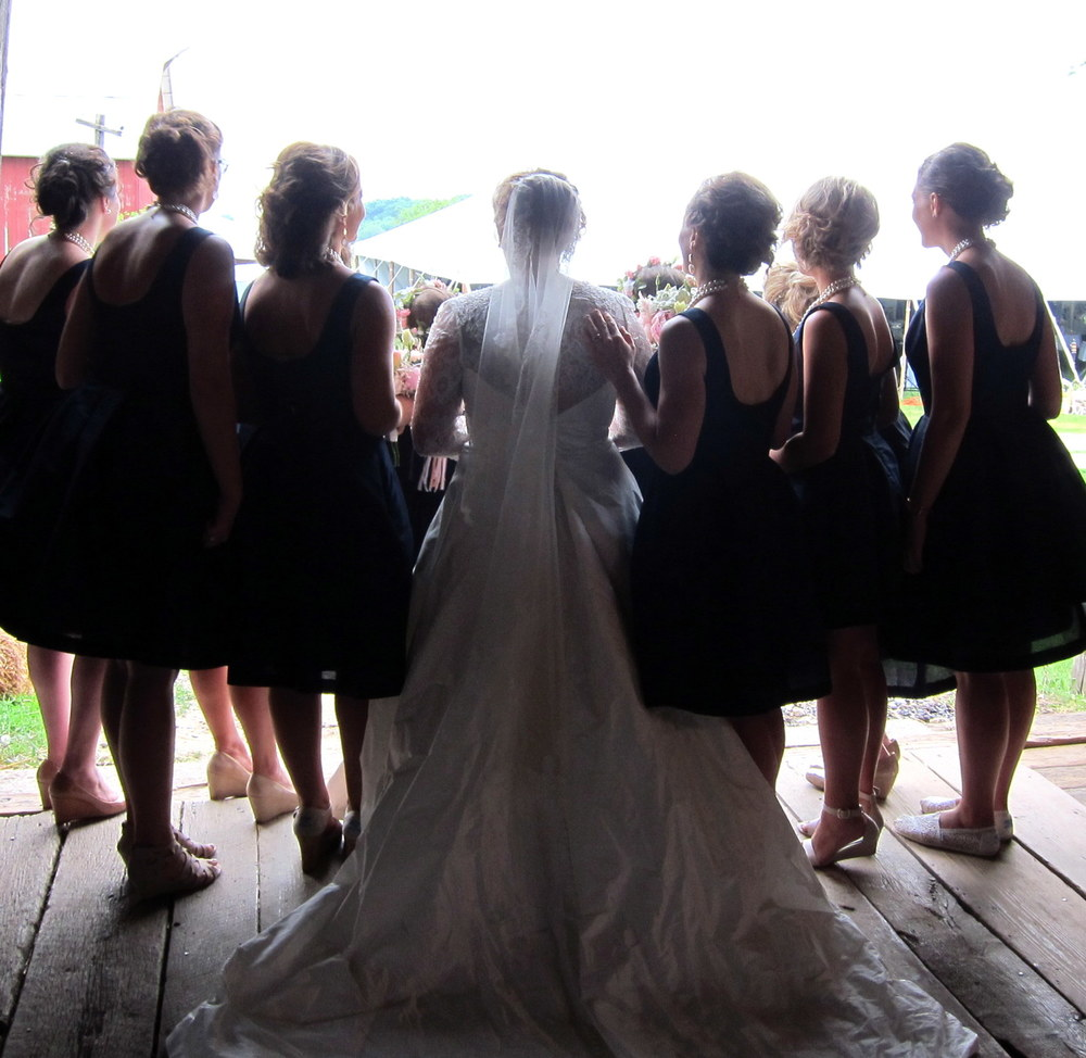 bride with bridesmaids exiting barn