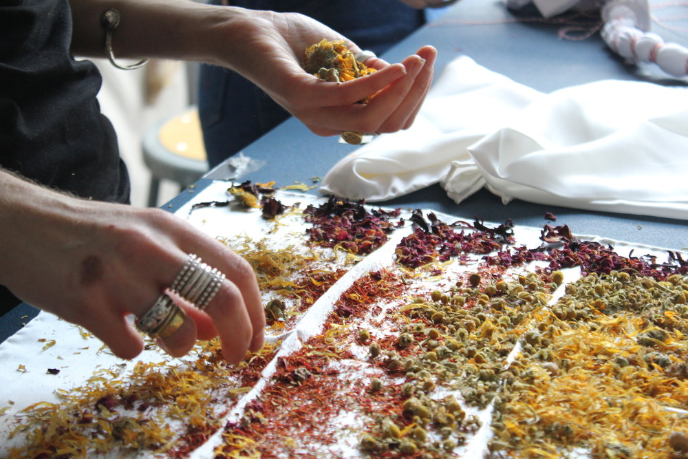 Arranging dried marigold, rose buds, safflower, chamomile, and hibiscus for a flower bundle. These give off a lovely scent while stewing in the dye vat.