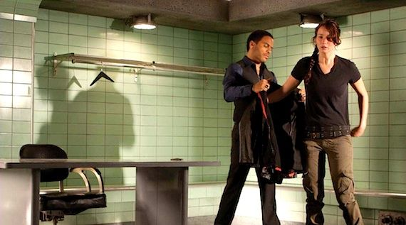Cinna (Lenny Kravitz) helps Katniss on with her jacket in The Hunger Games.