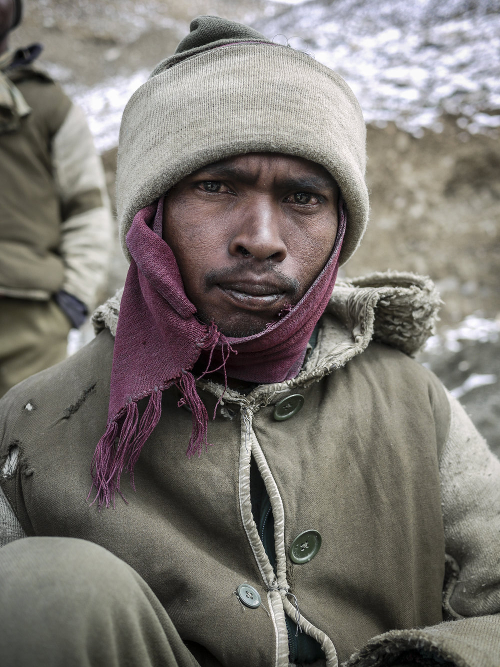 A young Bihari covers his ears in his  gamucha , literally 'sweat towel'.