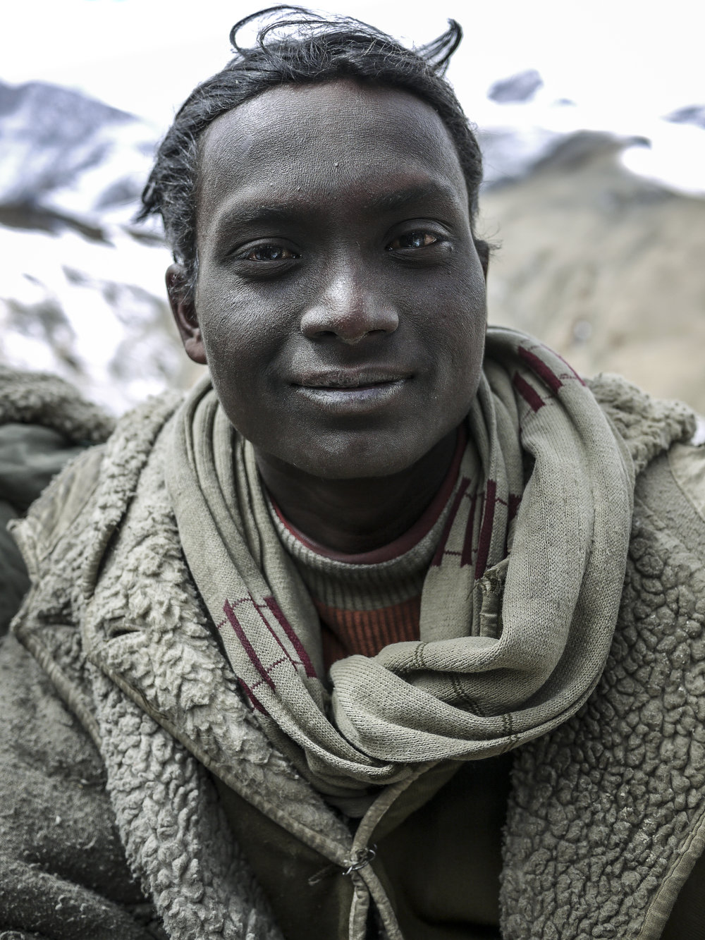 A young Bihari man with unusual coloured eyes. The effects of the high-altitude conditions are apparent on his face.
