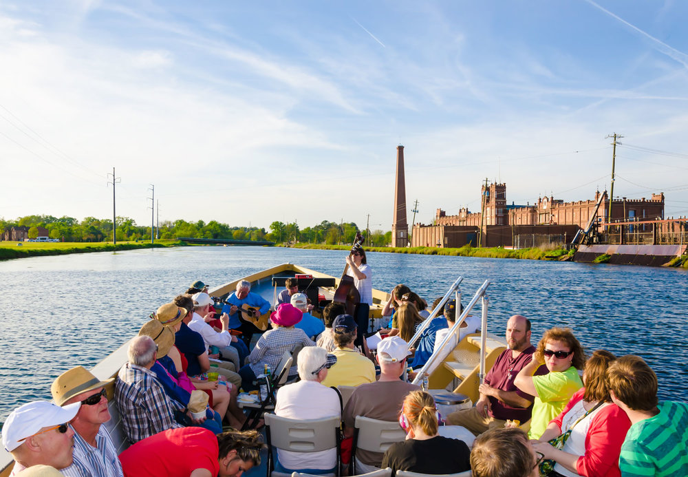 The Henrys play on the waterway of the Augusta Canal while visitors enjoy the Moonlight Music Cruise Petersburg Boat Tour. Call the Augusta Canal Discovery Center for more info.