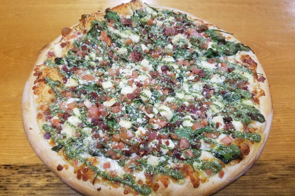 Phil Collins  Olive oil base, mozzarella, fresh spinach, tomato, garlic, bacon, feta finished with a pesto drizzle  S 9.99  L 19.99