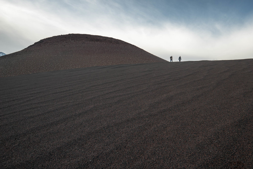 The wind-swept sand dunes shift from a scarlet red to a mystifying blackened hue.