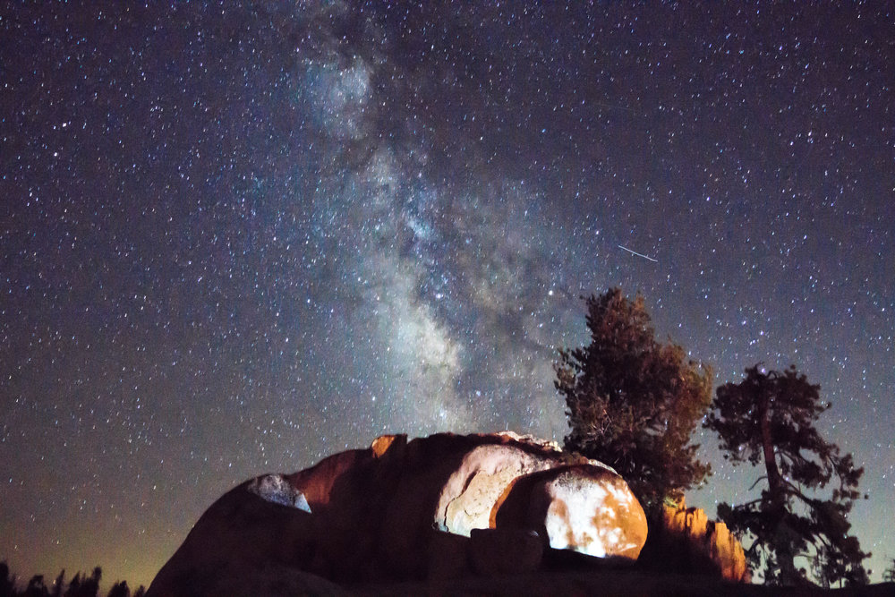 The Milky Way dances across the sky as the fire lights up some nearby boulders.