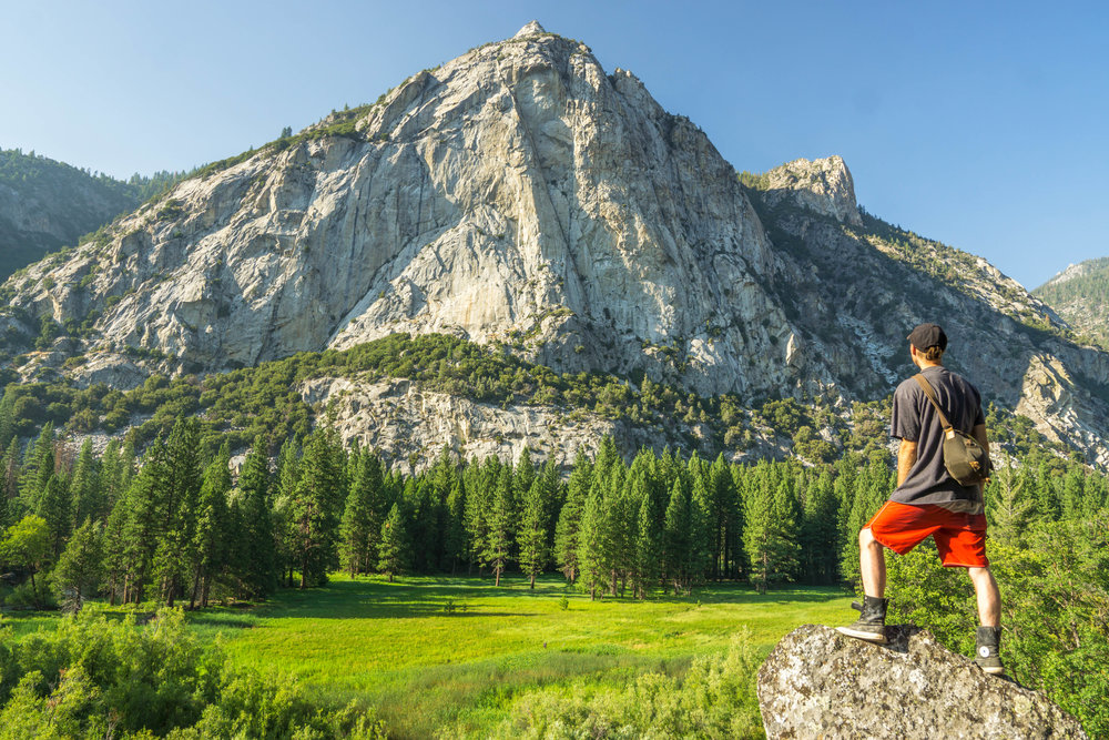 Like a small lake of green, the pine-rimmed meadow sets a stage for a giant granite dome, standing like a lone fortress.