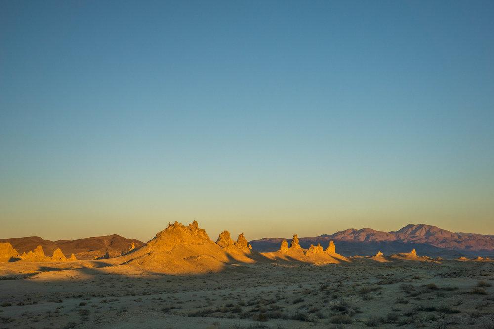 Golden orange cloaks the pinnacles while the shadows dance across the desert.