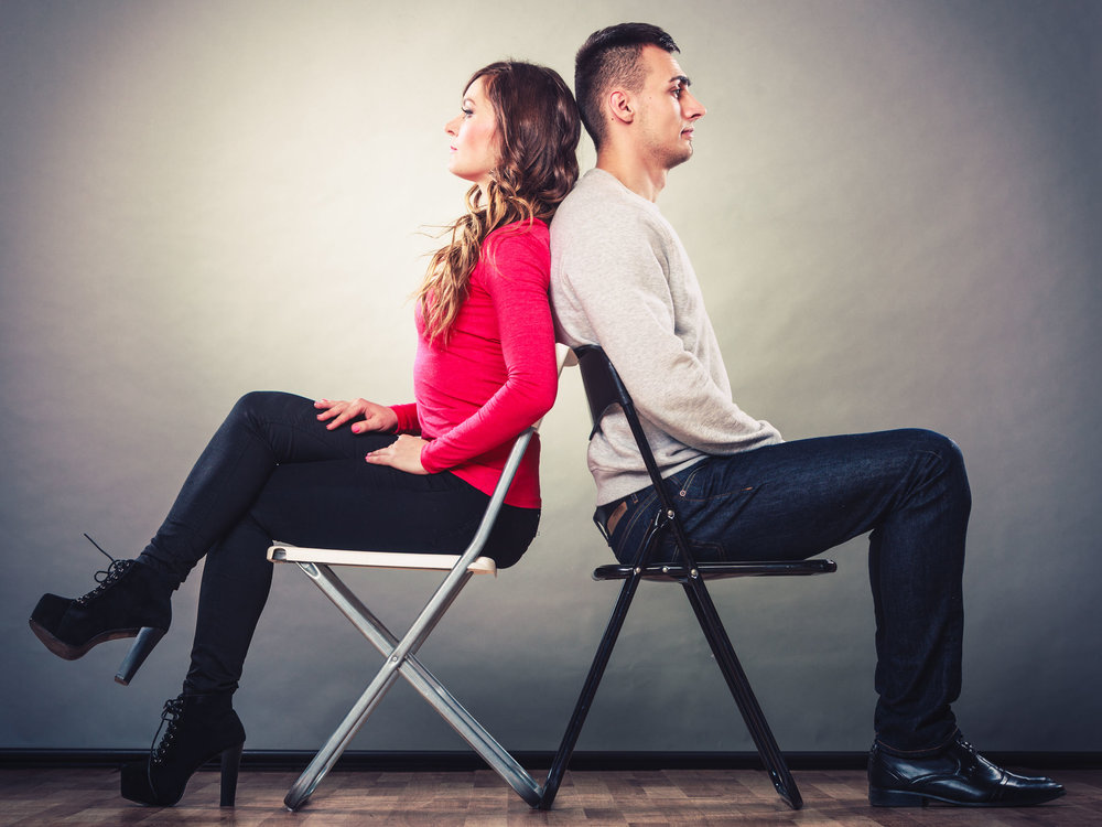 Irritated looking man and woman sitting on chairs with their backs together