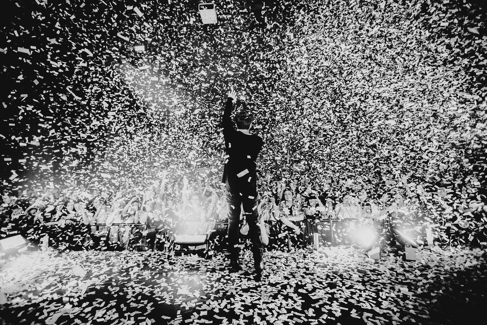 I cranked my shutter speed to 1/1000 for this photo because I didn't want the confetti falling down to be blurry. Shooting in manual and being able to change my shutter speed quickly let me get this moment. (Hoodie Allen in Seattle, WA)   Settings : Shutter Speed 1/1000, Aperture f/2.8, ISO 1000   Gear :  Canon EOS 6D ,  Canon 16-35mm f/2.8L II