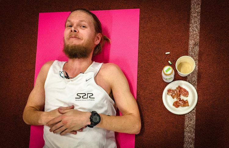 Henrik Roos tar en paus under 24-timmarsloppet på Personliga Rekordens Tävling 2017. Han fikar på bacon, fett-kaffe, saltkapslar och BCCA-kapslar.