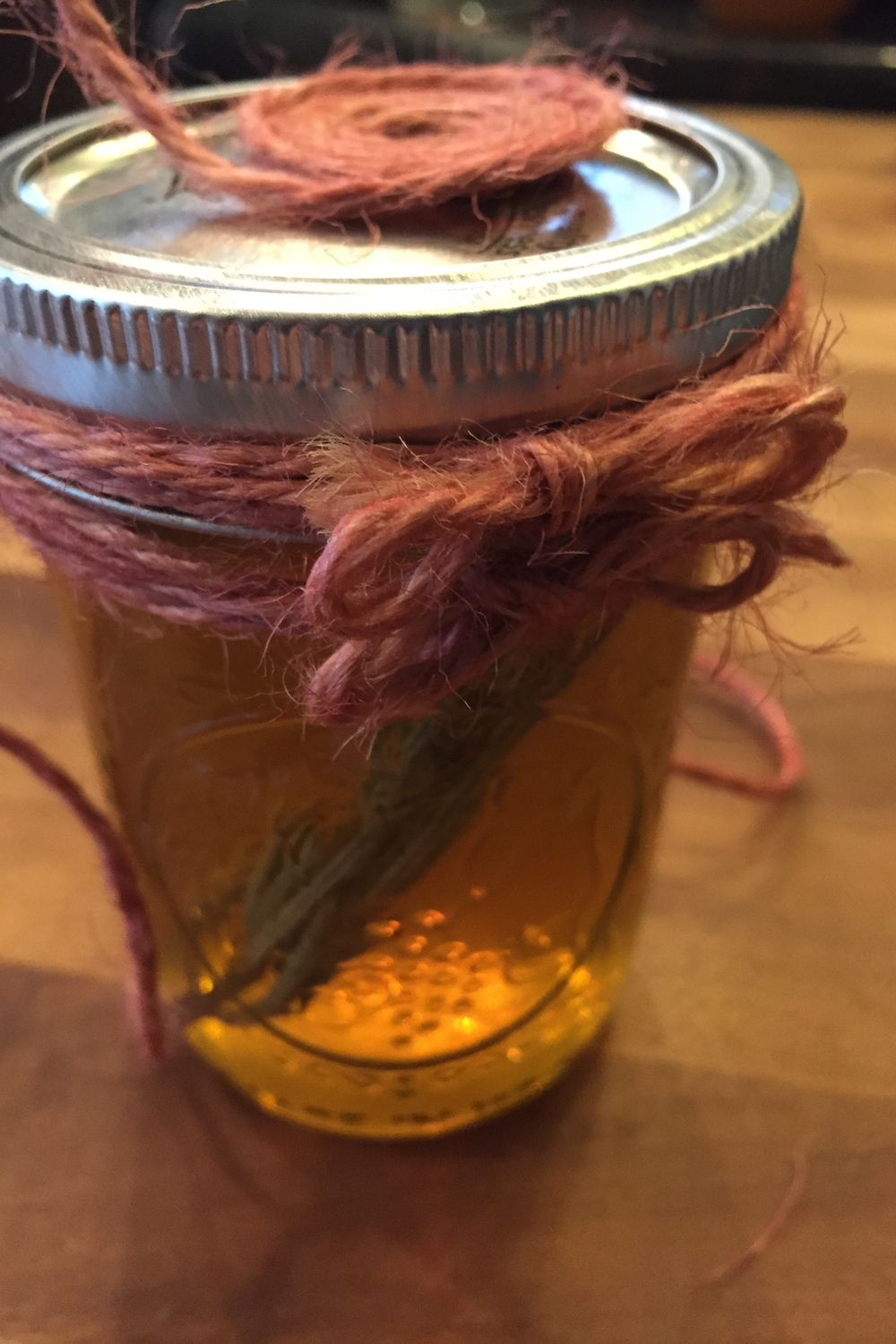 After you tie the twine bows around the jar, then work on the top. This will make designing the top easier. Fill in any gaps by wrapping more twine around the jar and knot.