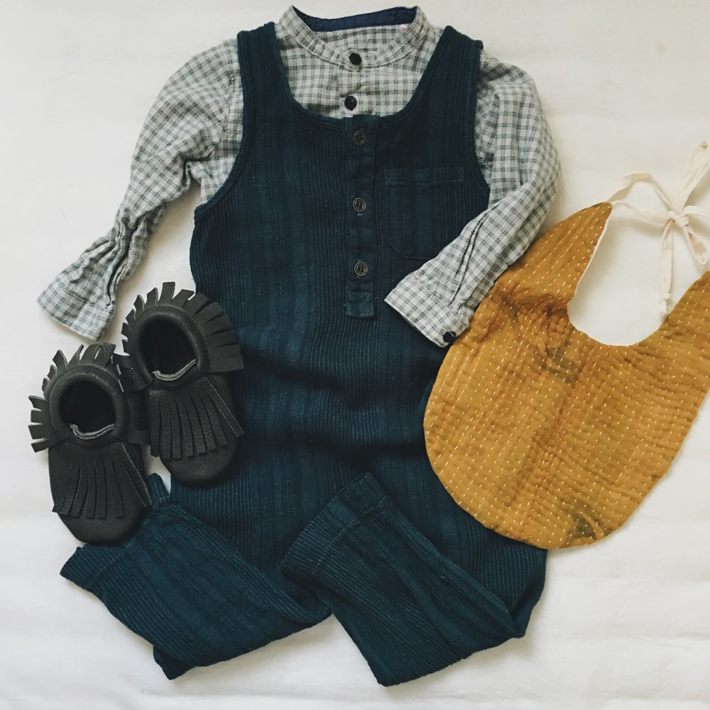 Romper - Nico Nico Clothing c/o Murray & Finn ; Plaid Shirt - Zara ; Bib - Wild Winnie ; Raven Moccasins c/o Little Pine Outfitters