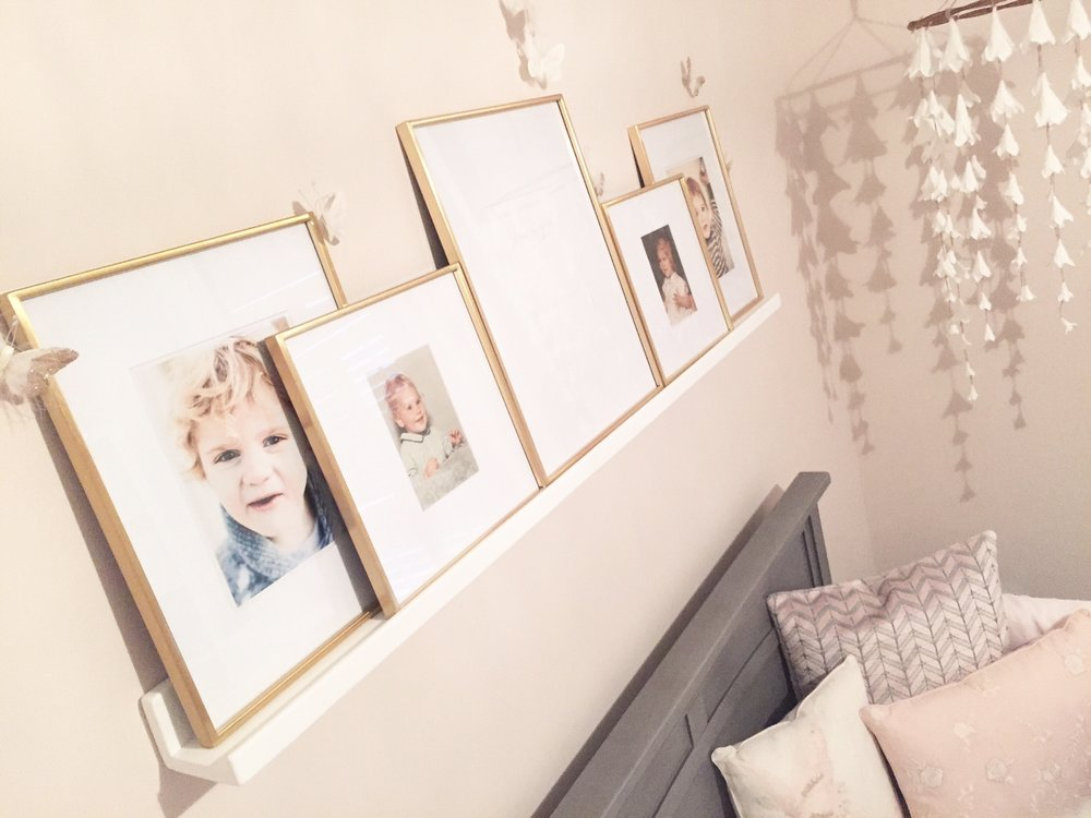 A picture ledge above the crib showcases baby pictures of the family with a special place for Baby Girl to be added.
