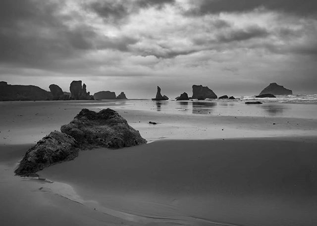 Bandon Beach, Oregon  The coast of Oregon and especially Bandon Beach is one of the most beautiful places on the planet, even on dark, dreary, and rainy days like this. Despite the weather I wasn't about to skip Bandon Beach as I know it will likely be a while before I'd get another chance to visit.  I had a short lull in the downpours to actually pull the camera out for a bit, even with the lull I had to pull out the rain gear and wipe off the front element about every 30 seconds lol.  You can see the famous Wizard Hat rock formation in the distance.  Next year I plan to spend a lot more time on the Oregon Coast then the tease that was this summer's trip.  I've been coast to coast from Nova Scotia, Acadia, and the costs of North & South Carolina to the entire California coast line and despite the unique beauty of all of those places there is something quite special about the coast of Oregon!  #oregon #bandonbeach #oregoncoast #moody #traveloregon #oregonbeach #beach #coast #landscapephotography #landscapes #sony #wanderlust #travelbug #nature #rain