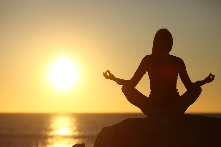 A photo of a woman meditating on the beach, by the sunset