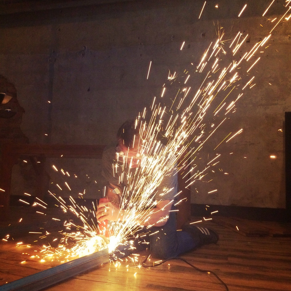 Phillip Viohl in a shower of sparks, cutting down one of the tables to make room for the new booths at The Square