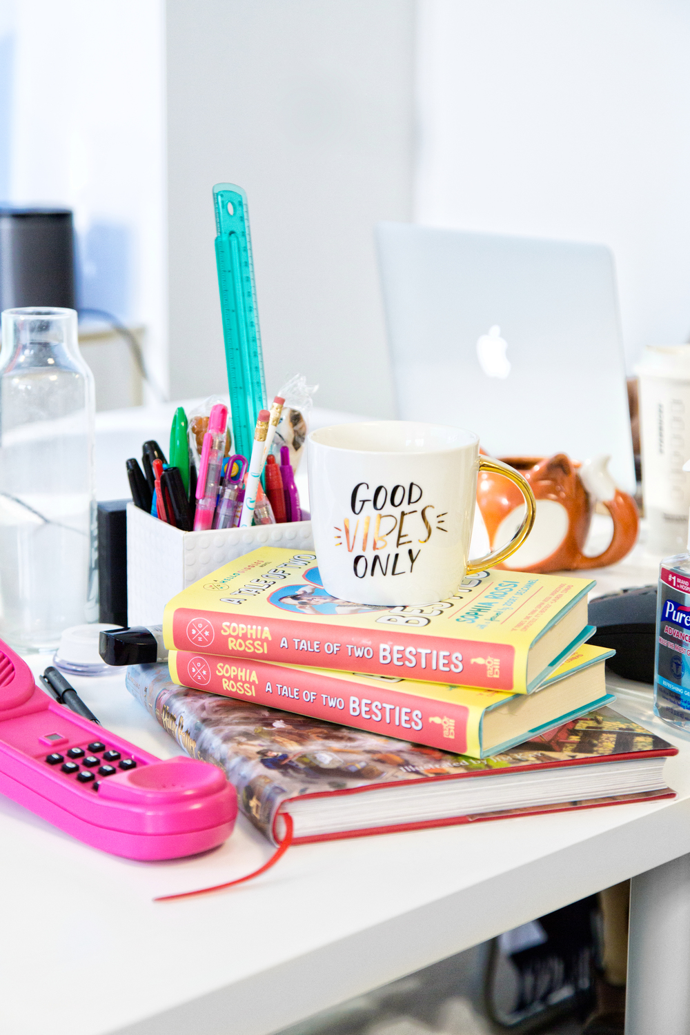 """On the desk, copies of Sophia's latest book, """" A Tale of Two Besties: A Hello Giggles Novel. """" Aforementioned Dream Phone. And a peppy mug. The usual."""