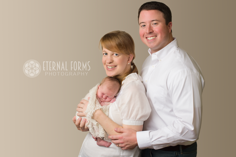 Proud mommy and daddy pose with their newborn for their first family portrait