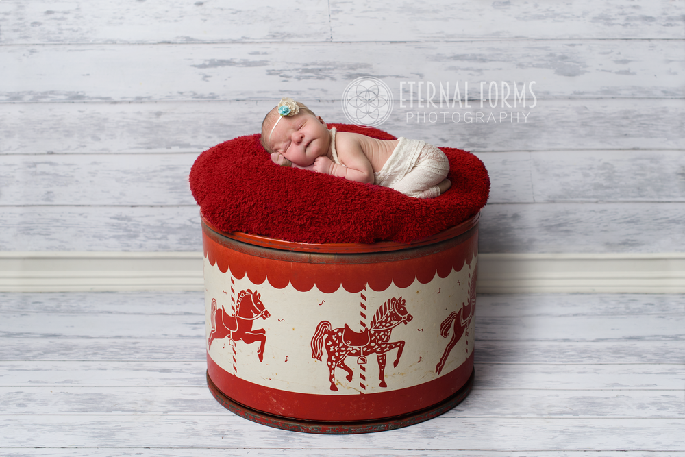 newborn on antique toy box (headband crafted by Michelle)