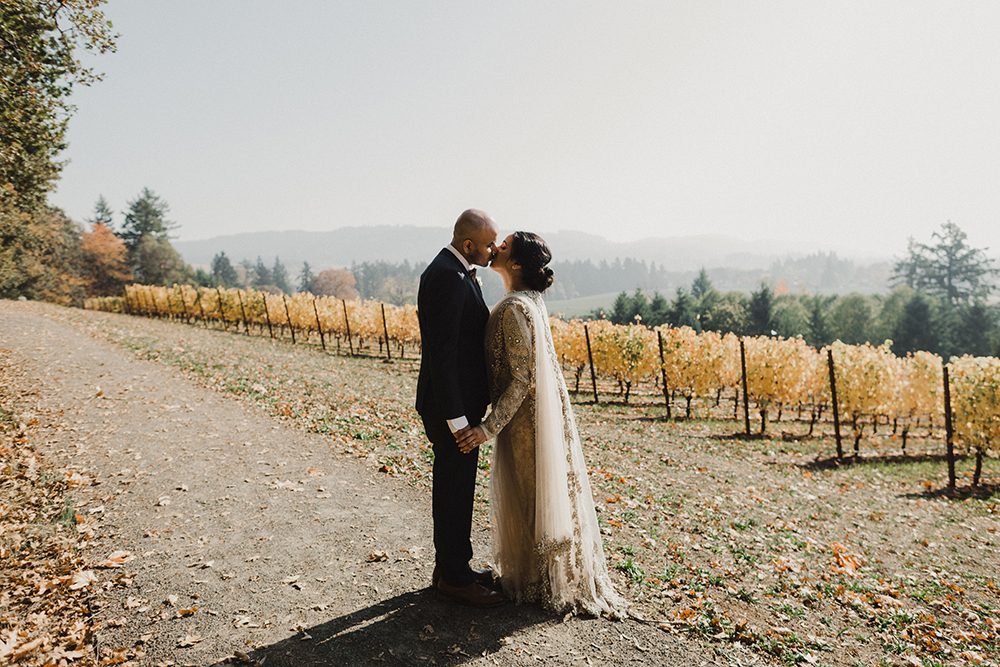 Bride and groom kissing with vineyards in background