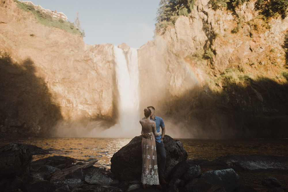 Engaged couple kissing in front of falls