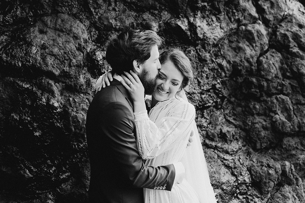 groom kissing bride next to rocks with pure happiness