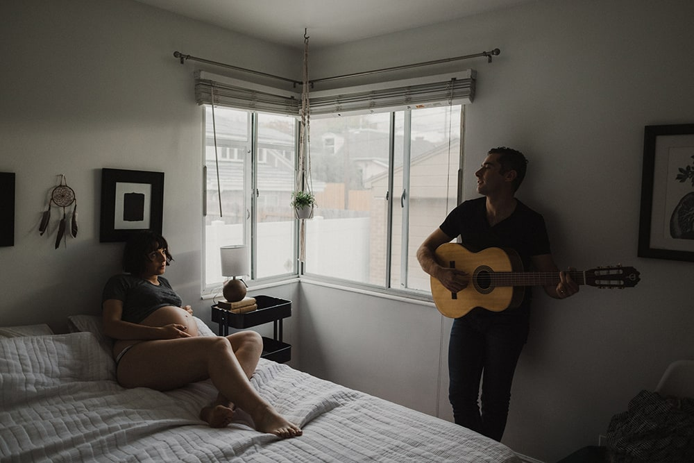 man playing guitar for pregnant wife