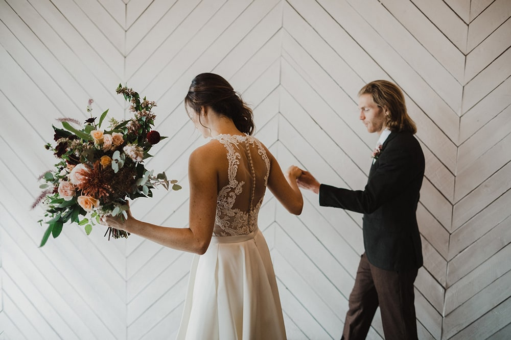 bride and groom walking down stairs while bride holds bouquet