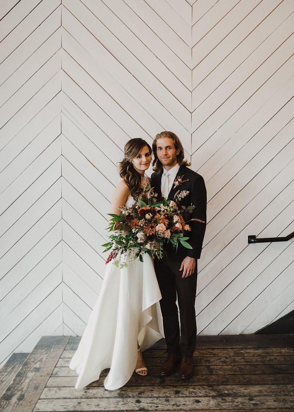 bride and groom smiling at camera with bouquet