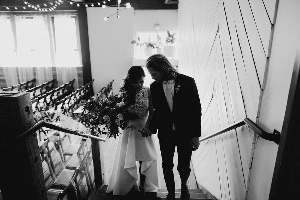 bride and groom walking up stairs before ceremony
