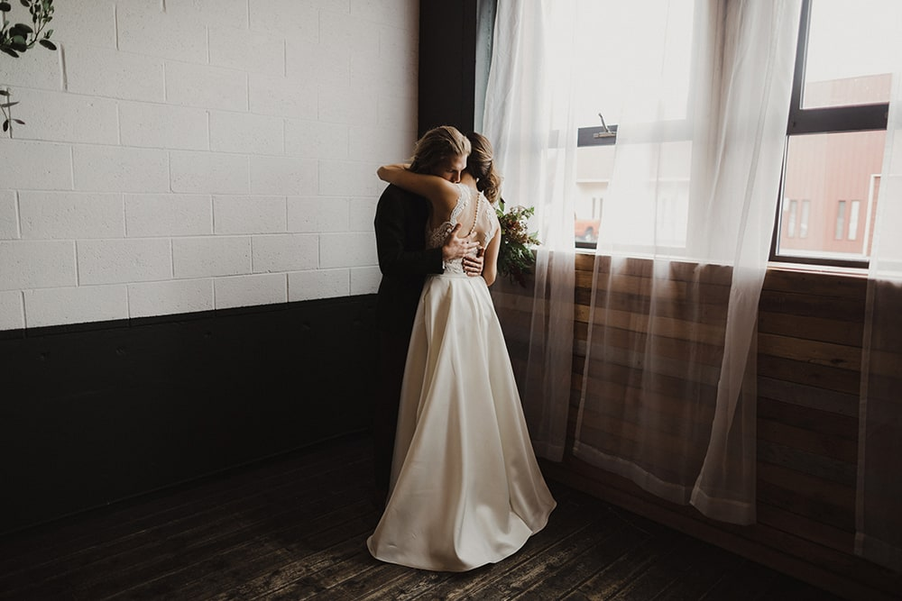 couple cuddling next to window with natural light