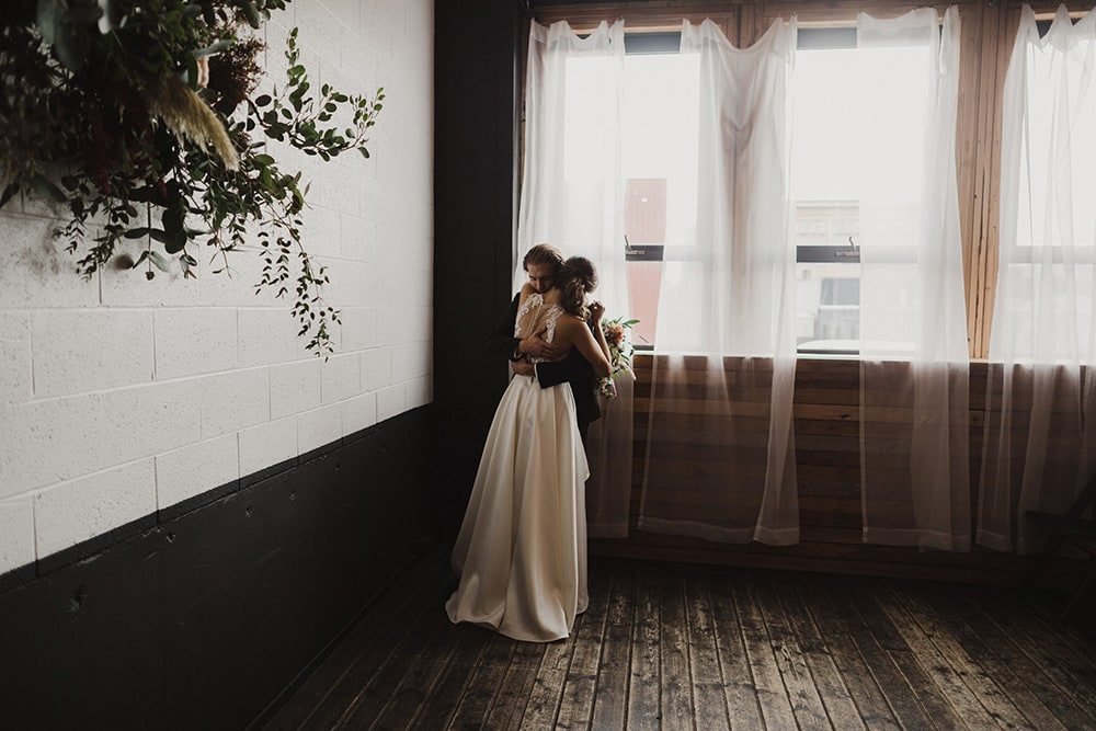 couple hugging and kissing in front of window
