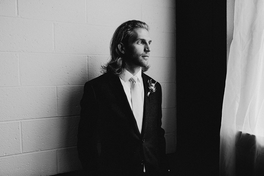 groom looking out window in black and white photo