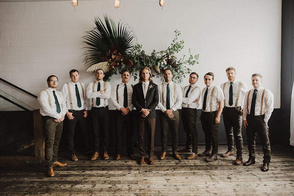 groom and groomsmen holding hands at waist