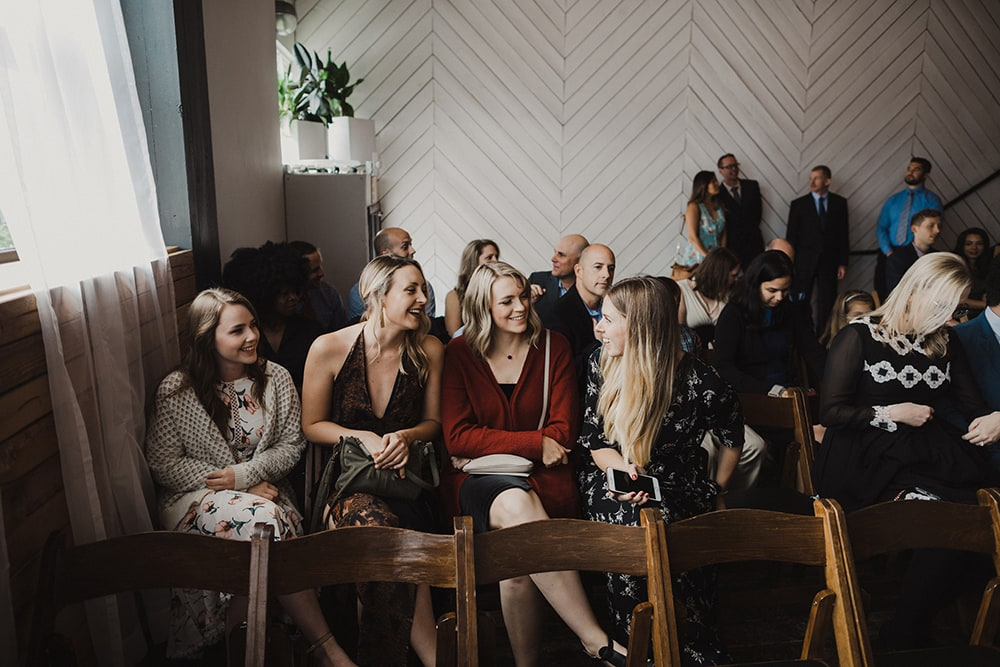 guests smiling and laughing while waiting for wedding ceremony