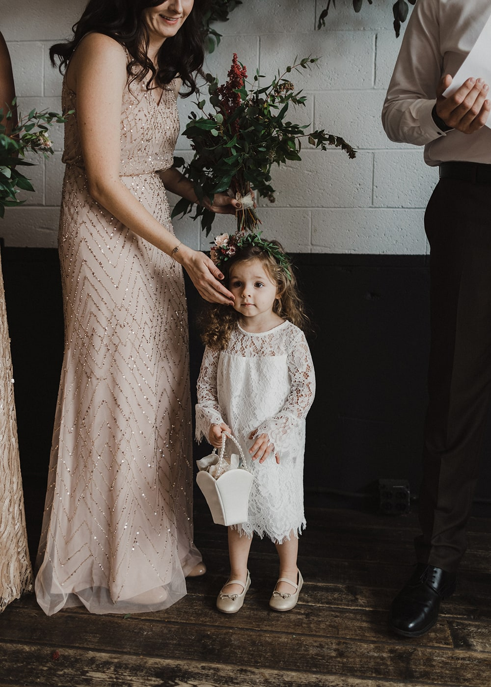 little flower girl with mother holding her cheek